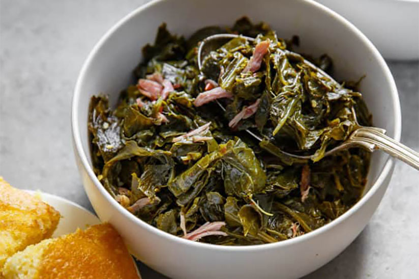 Spoon scooping up collard greens in white bowl on counter