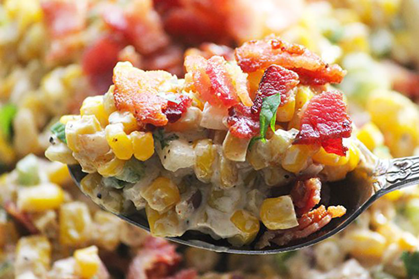 Spoonful of corn dip topped with chopped bacon