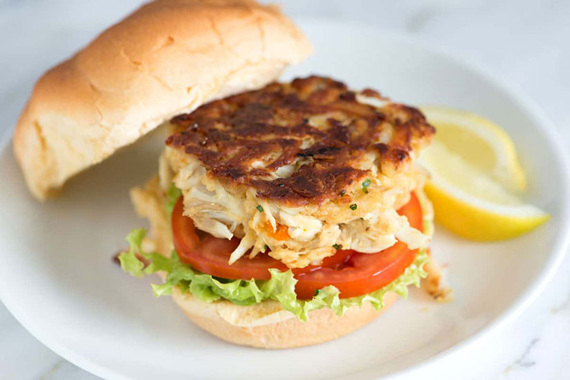 Crab cake sandwich with side of lemon slices on white plate