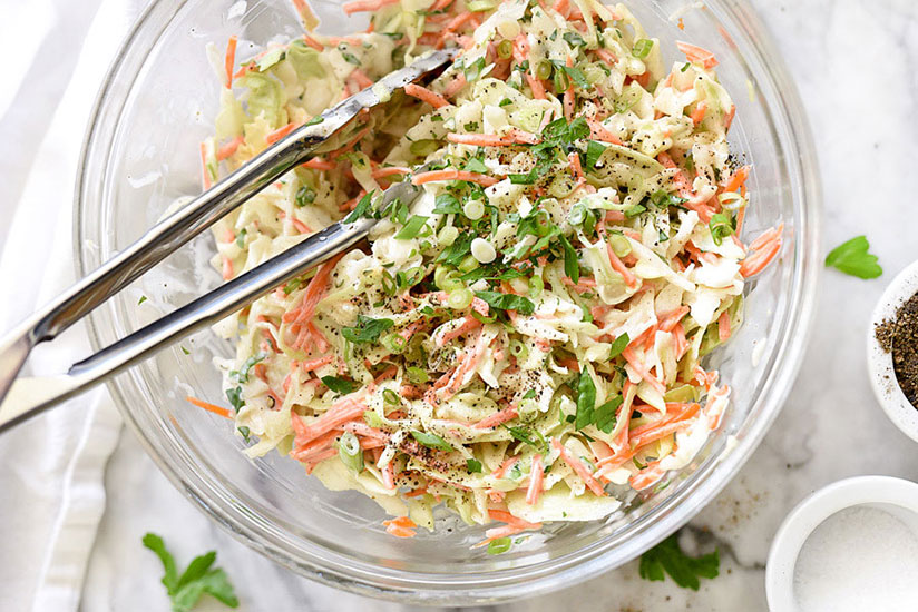 Coleslaw topped with chopped herbs in clear bowl with tongs on counter