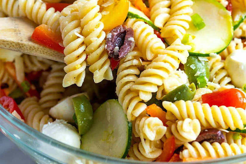 Pasta salad with sliced zucchinis and tomatoes in clear bowl