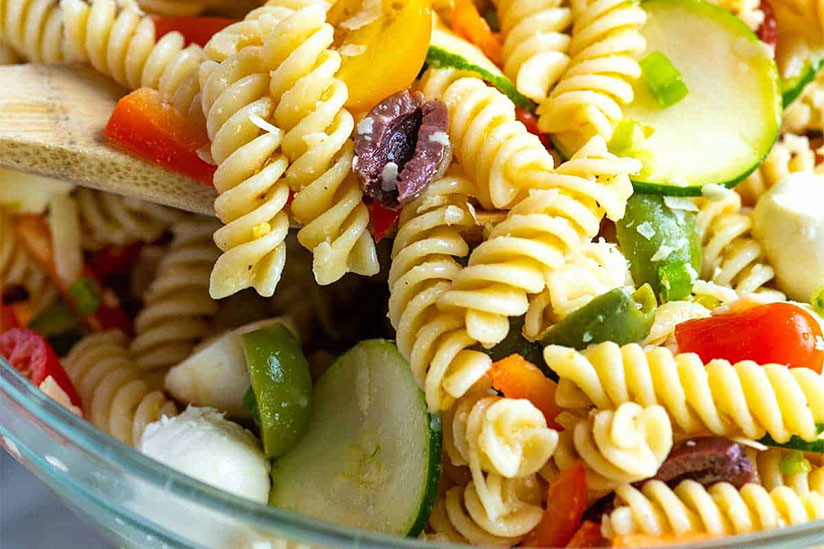 Pasta salad with sliced cucumbers and lemon in clear bowl