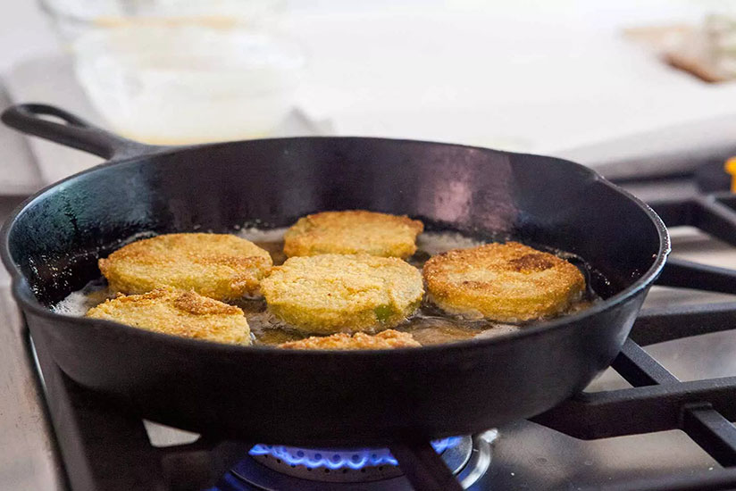 Breaded tomatoes cooking in oil in iron skillet on stove