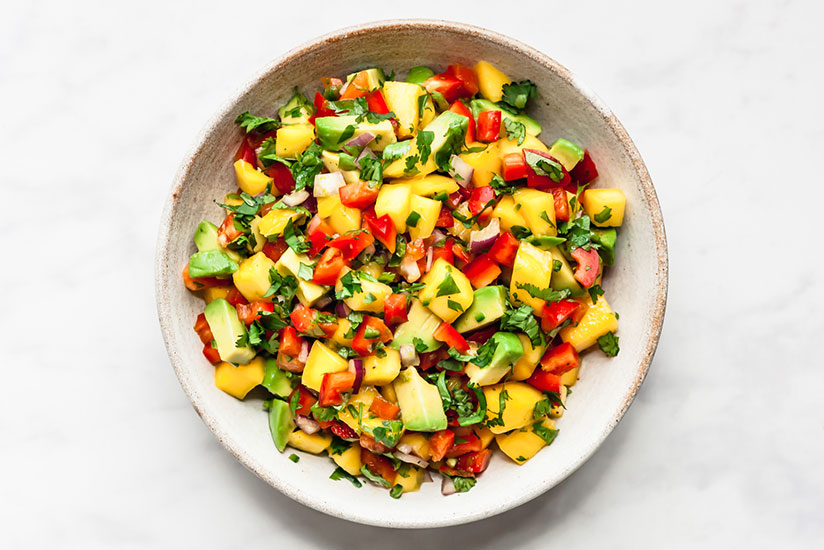 Mango salsa sprinkled with chopped herbs on white plate on counter