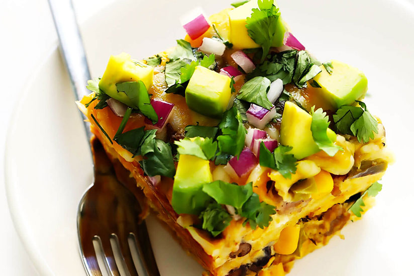 Portion of Mexican breakfast casserole with sliced avocados on plate