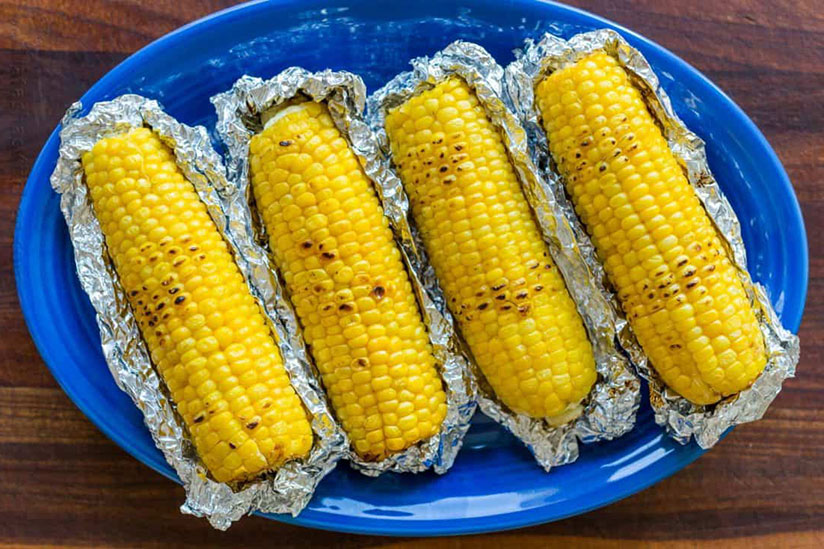 Four grilled corn on cob on blue plate on wood counter
