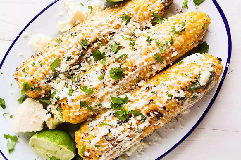 Grilled Mexican corn topped with herbs on blue and white plate