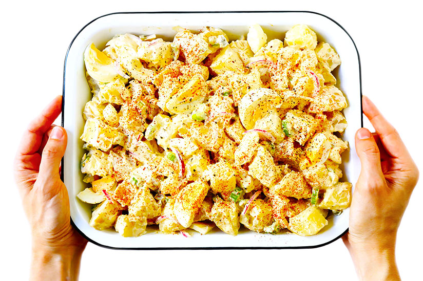 Hands holding potato salad in white dish on white background