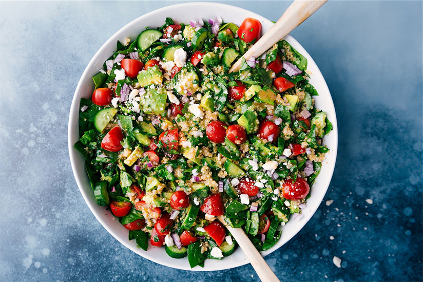 Quinoa salad with wood salad spoon and fork in white bowl