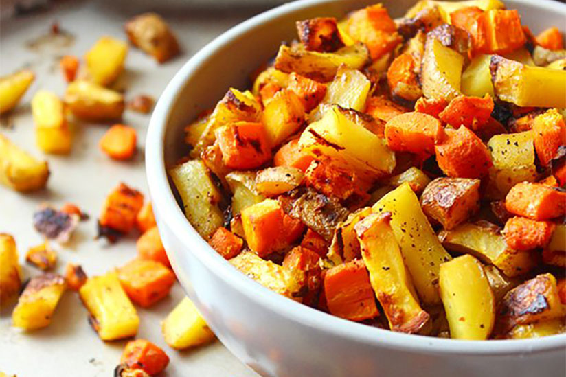 Roasted carrots and potatoes in white bowl on metal tray