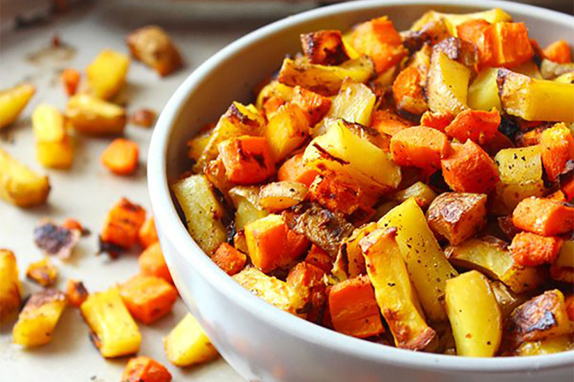 Sliced roasted carrots and potatoes in white bowl on tray