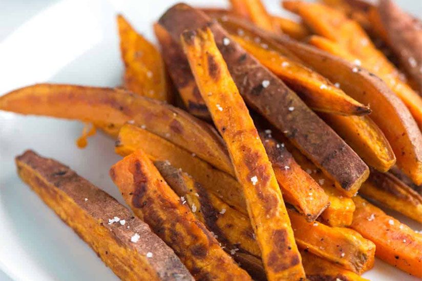 Baked sweet potato fries sprinkled with salt on white plate
