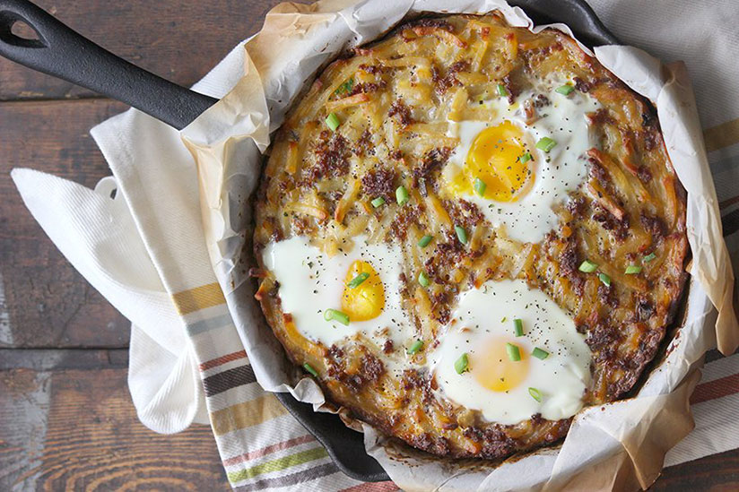 Sausage egg hash brown with green onions in iron skillet on counter