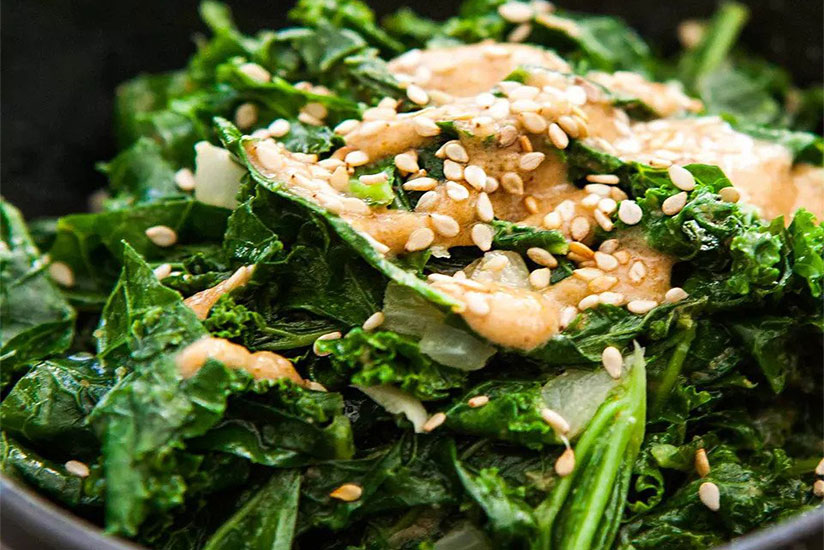 Sauteed kale with tahini sauce sprinkled with toasted sesame seeds in bowl
