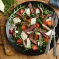 Seared steak, rocket, and tomato salad on black plate with two forks