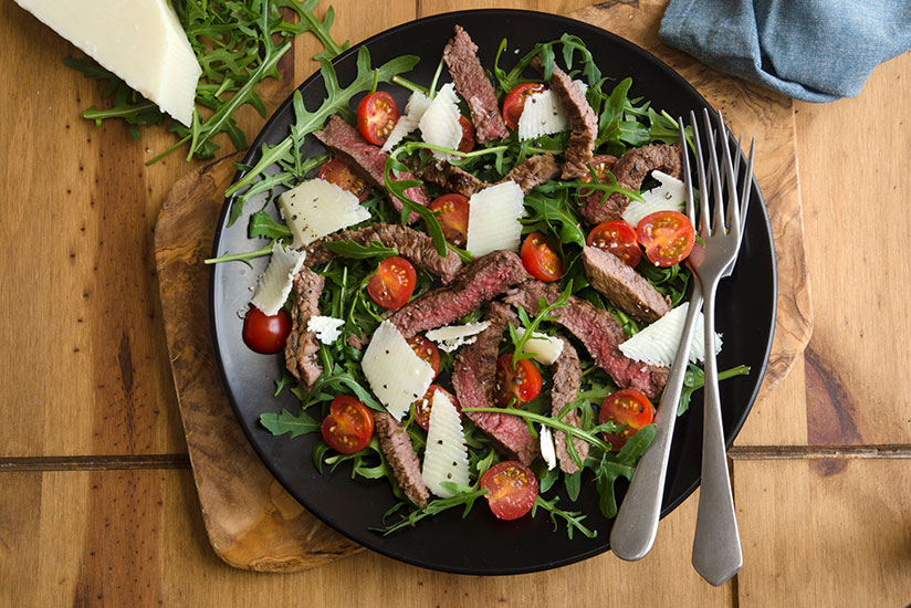 Rocket and tomato salad with slices of steak on black plate on wood counter