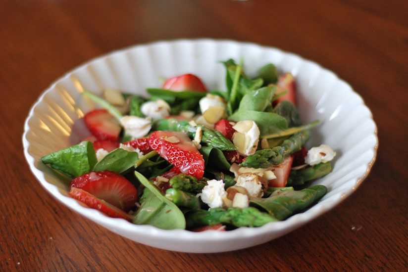 Strawberry spinach salad on white plate on wood counter