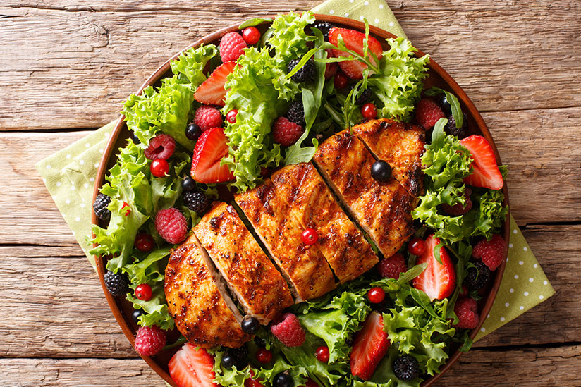 Sliced grilled chicken on lettuce with summer berries on brown plate
