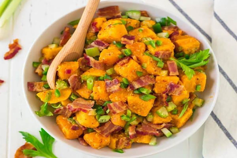 Sweet potato salad in white bowl with wooden spoon on counter