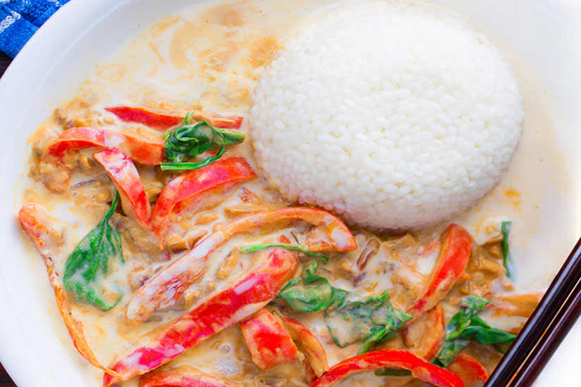 Thai coconut curry served with cup of white rice on plate with chopsticks