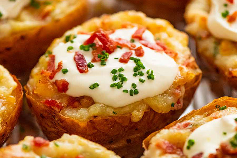 Baked potatoes topped with sour cream, bacon, and herbs on tray