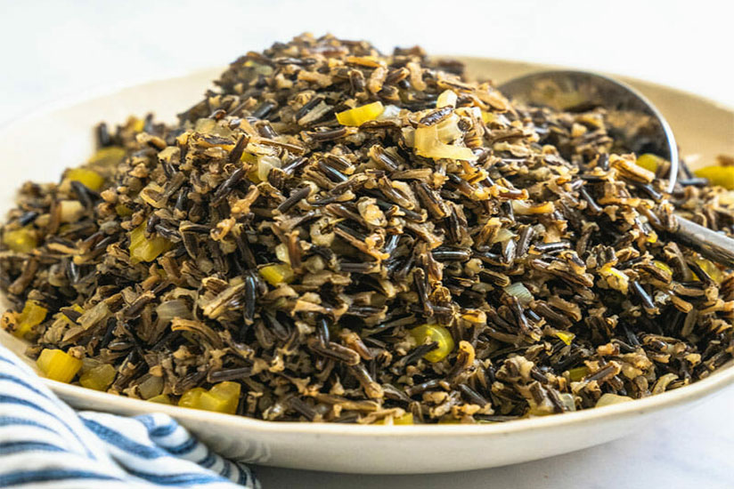 Wild rice on white plate with spoon on marble counter