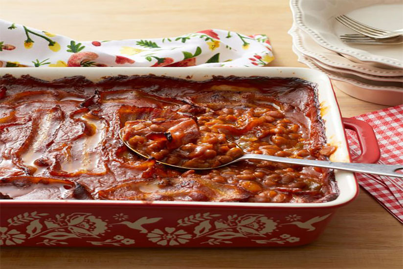 Baked beans in red dish with spoon on wood counter
