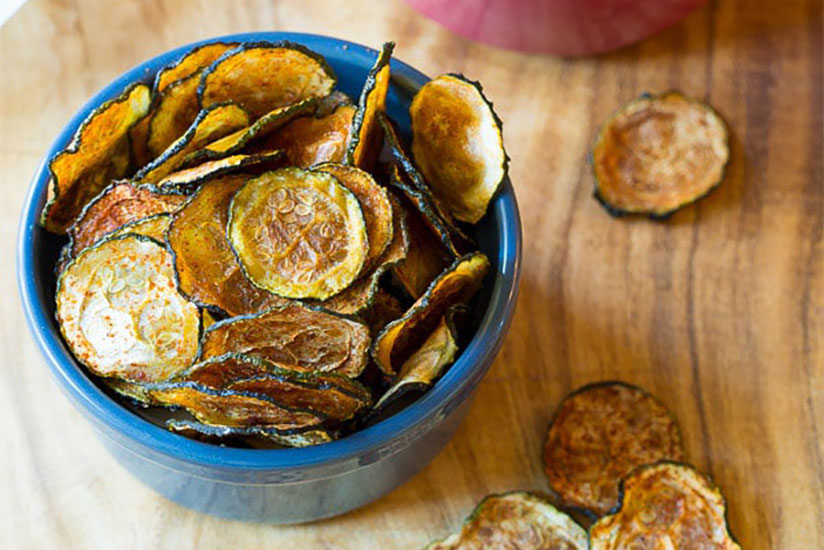 Baked zucchini chips in blue bowl on wood counter