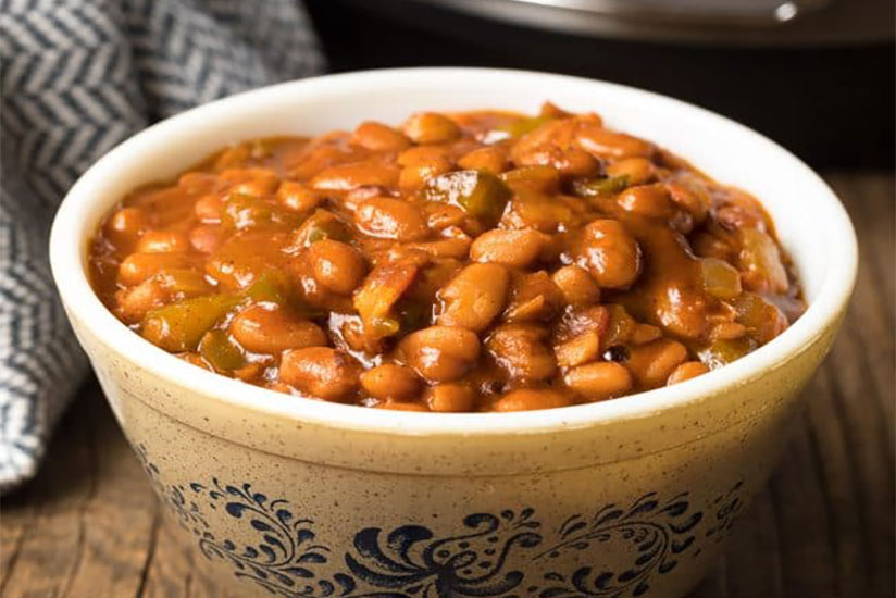 Instant pot baked beans in white bowl on wood counter