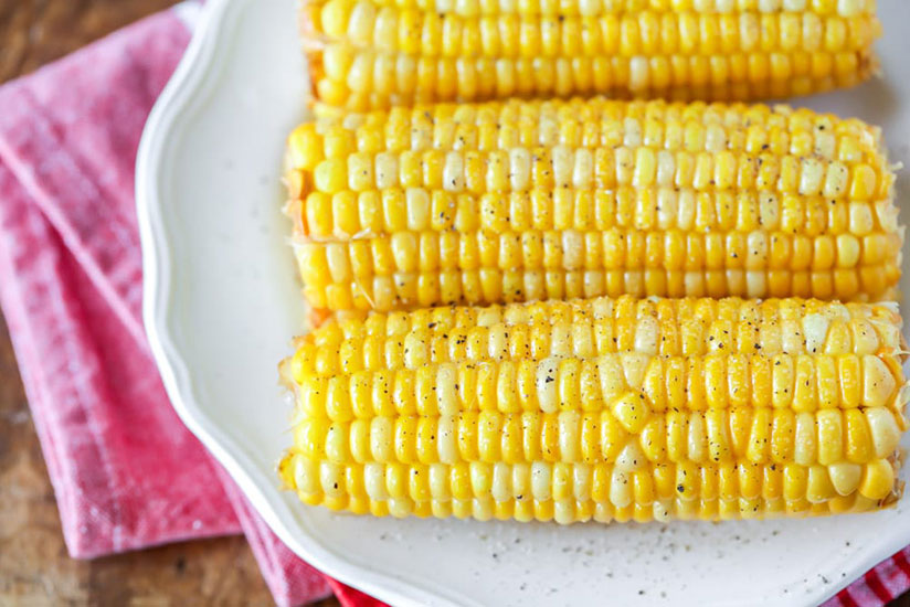 Three corn on a cob on white plate on wood counter