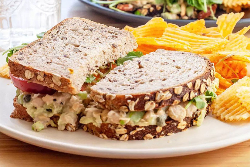 Sliced chickpea salad sandwich on white plate with side of chips