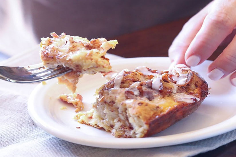 Woman cutting cinnamon breakfast roll with fork on white plate