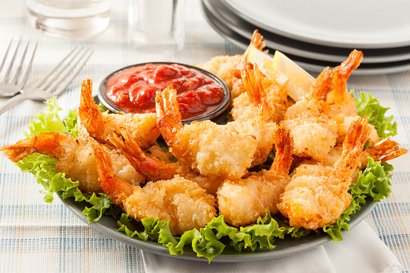 Fried coconut shrimps on bed of lettuce on plate beside dipping sauce