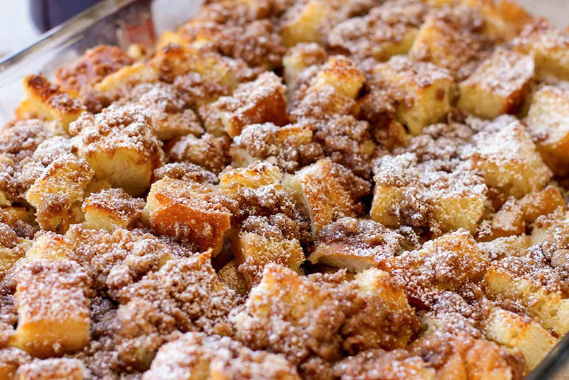Golden brown French toast bake with cinnamon in clear dish