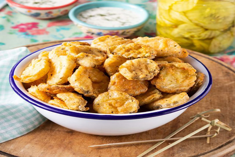 Battered fried pickles in blue and white bowl on wood tray