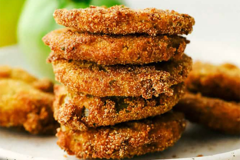 Stack of breaded fried tomatoes on white counter
