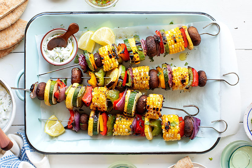 Grilled vegetables on skewers with side of dipping sauce on plate