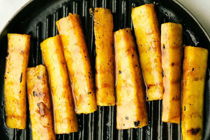 Nine grilled pineapple spears on grill pan on white counter