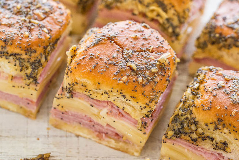 Ham and cheese sliders with poppy seeds on white counter