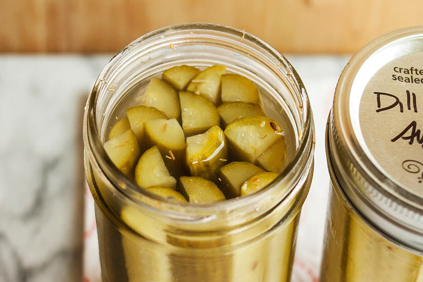 Dill pickle spears in clear jar on brown and white background