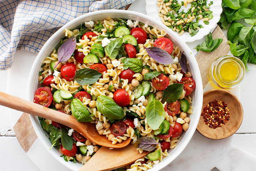 Pasta salad with tomatoes and cucumbers in white bowl on counter