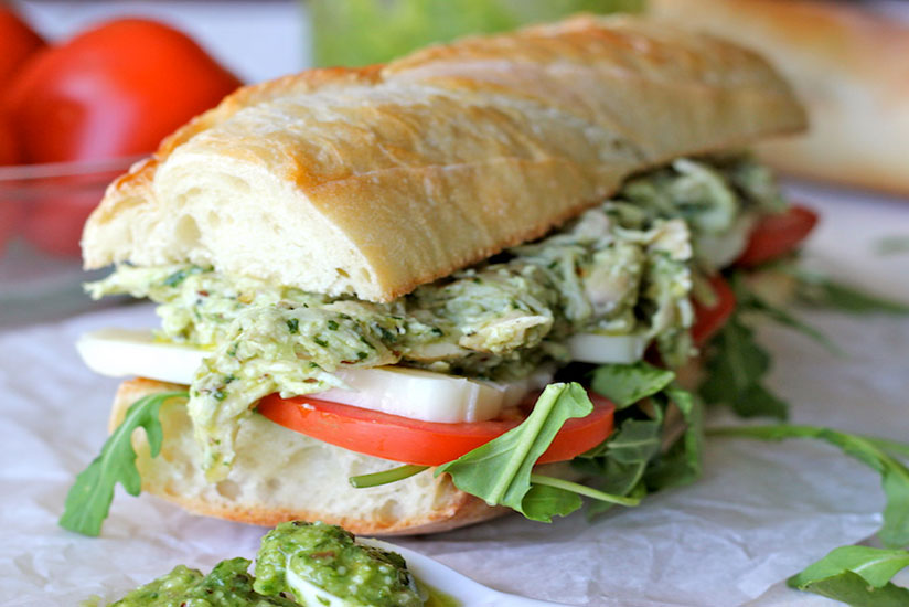 Pesto chicken sandwich with tomatoes on top of wax paper