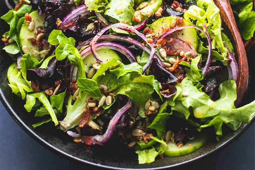Green salad with sliced red onions in black bowl on counter