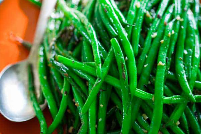 Steamed green beans on orange plate with metal spoon