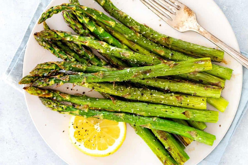 Steamed asparagus spears with slice of lemon on white plate