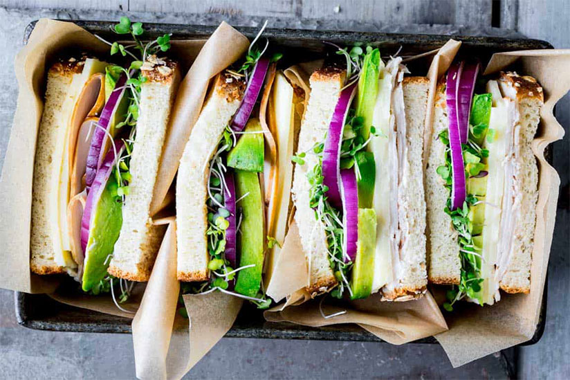 Turkey sandwiches with avocado and sprouts in black container