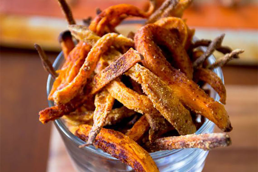 baked crispy sweet potato fries overflowing from clear glass on counter