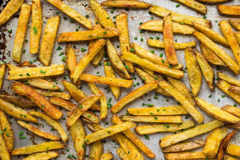 Homemade baked French fries sprinkled with chopped herbs on tray