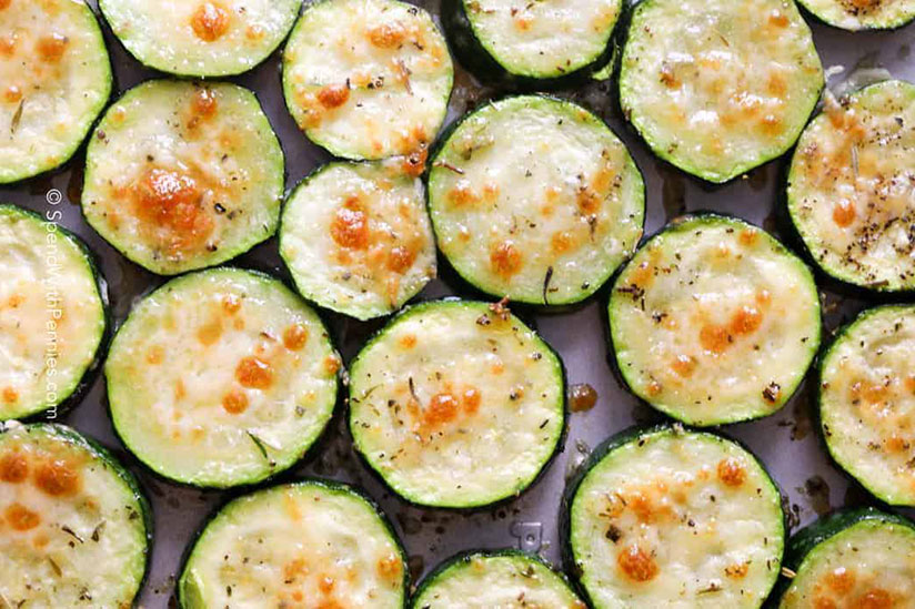 Oven baked sliced zucchinis topped with melted cheese on tray