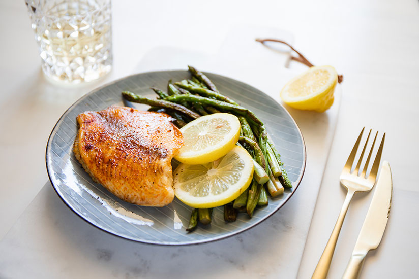 Baked tilapia served with asparagus stalks and lime slices on blue plate